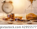 Hourglass and currency on table, Time Investment 42955577