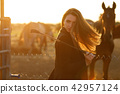 rider woman with whip at the sunset 42957124