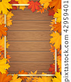 Frame with fallen maple leaves on wooden background. 42959401
