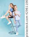 Girls twins in light blue clothes are posing near a bar stool on a blue background. 42961106