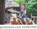 Cute asian child girl riding a pony in the farm 42965906