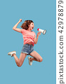 Beautiful young woman jumping with megaphone isolated over blue background 42978879