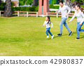 Little girl is running with parents in the park.  42980837