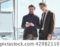 Businesspeople at office working together standing browsing inte 42982110