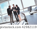Businesspeople at office working together standing man browsing 42982119