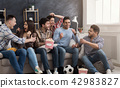 Excited friends watching football match at home 42983827