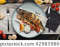 Grilled fish on plate at restaurant table 42983980
