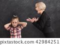 Grandmother arguing her little granddaughter 42984251