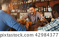 Men drinking beer and communicating with bartender 42984377