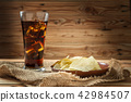 Potato chips with cola on a wooden background 42984507