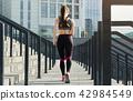 Back view of slim woman running on stadium stairs 42984549