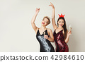 Happy girls in fashion dresses drinking champagne at white background 42984610