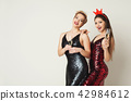 Happy girls in fashion dresses drinking champagne at white background 42984612
