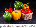 Three sweet peppers on a wooden 42985854