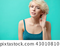 A hard-of-hearing young beautiful woman putting her hand to her ear 43010810