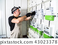 Electrician engineer works on fuse switch box 43023378