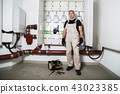 Electrician standing near distribution board 43023385