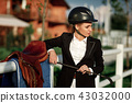 elegant rider woman in helmet with whip 43032000