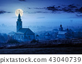 catholic and orthodox churches at foggy night 43040739