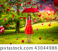 Woman in red dress with umbrella in summer park 43044986