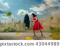 Woman in red dress with umbrella, hurricane 43044989