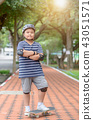Obese boy learn to ride skate board in park 43051571
