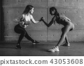 Fit woman wrestle on hands with a female opponent looking in her eyes. 43053608