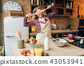 Housewife covers her eyes with wooden spatulas 43053941