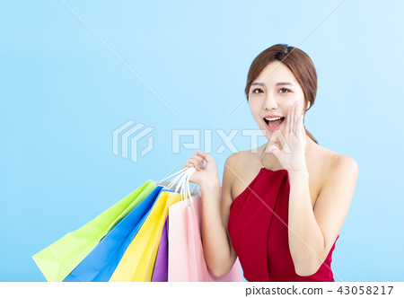 young Woman holding shopping bags and shouting 43058217