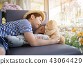 Lovely moment of asian cute boy playing with doll. 43064429