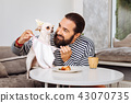Owner of dog sharing his piece of dessert with his dog 43070735