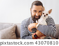 Dark-haired smiling man holding his lovely pet 43070810