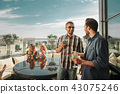 Two cheerful bearded men with alcohol drinks chatting while beautiful ladies sitting at the table on 43075246