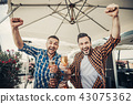Cheerful bearded men raising clenched hands and holding beer 43075362
