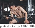 Joyful man is enjoying upper body workout indoors 43076186