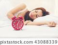 Selective focus red alarm clock front girl sleep 43088339