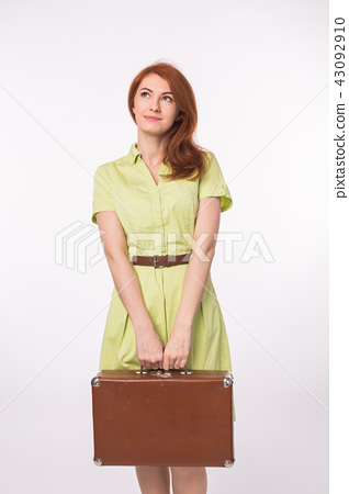 Redhead young woman holding retro suitcase on white background 43092910