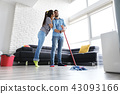 Man And Woman Kissing While Cleaning Home 43093166