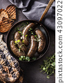 Roasted sausages in pan with bread and herbs. 43097022