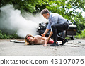 A man helping a young woman lying on the road after a car accident. 43107076