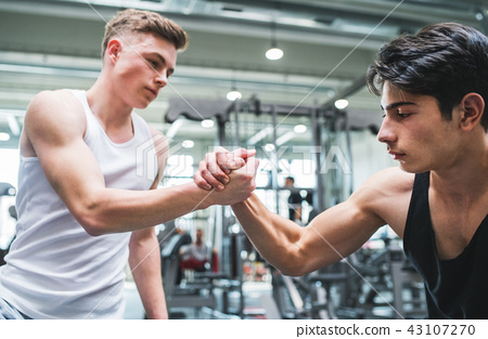 A friendly handshake of two young men in crossfit gym. 43107270
