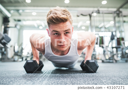 A close-up of young fit man in gym doing push ups on dumbbells. 43107271