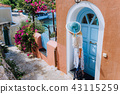 Travel tourist woman on vacation in Greece. Person with blue sunhat in front of traditional 43115259