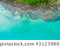 Rocky beach turquoise clear water with green tree 43123960