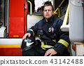 Photo of young fireman with helmet in overalls sits in fire truck 43142488