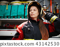 Photo of young fire woman with long hair in helmet next to fire engine 43142530