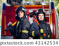 Photo of two firemen men in camera with axes in hands near fire engine 43142534