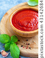Wooden bowl with spicy tomato sauce. 43142684