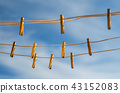 Clothespins on a clothesline against a blue sky 43152083