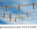 Clothespins on a clothesline against a blue sky 43152084